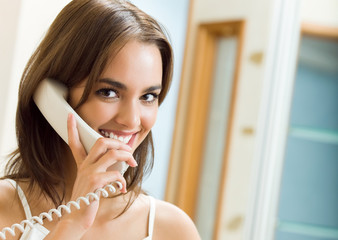 Cheerful woman talking on phone, at home