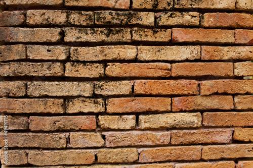 horizontal orange antique old brick wall with black humid fungus