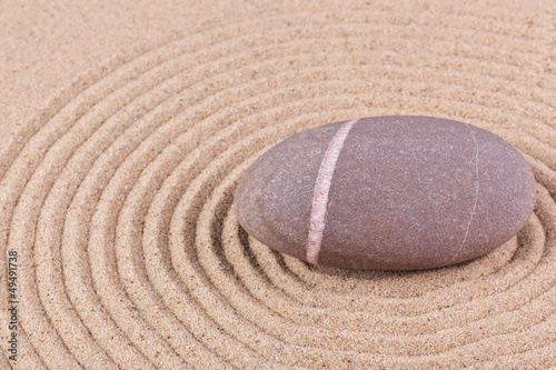 Pebble in a raked sand circle zen garden