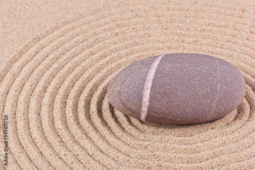 Pebble in a raked sand circle zen garden