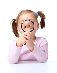 Cute little girl is playing with magnifier