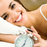 Woman with alarmclock on the bed