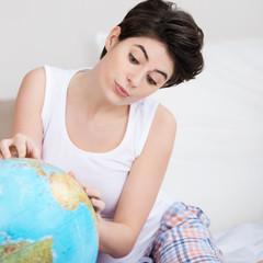 frau sucht ihr reiseziel auf dem globus