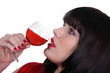 Striking shot of a woman drinking a glass of wine