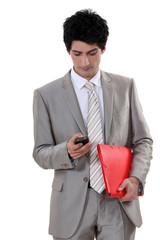 A businessman checking his cellphone.