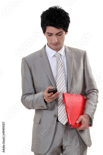 A businessman checking his cellphone.