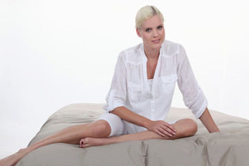 Blond woman sitting on bed