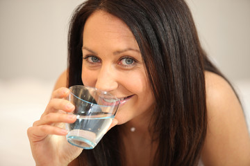Brunette drinking a glass of water