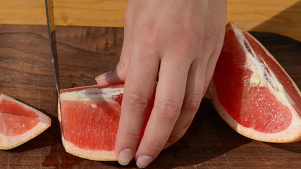 hand slice fresh ripe grapefruit pomelo fruit into pieces