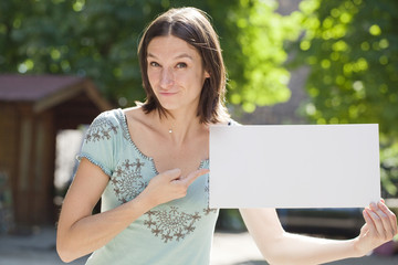 happy young woman showing something on a board