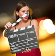 Woman In A Red Dress Holding Clapper Board