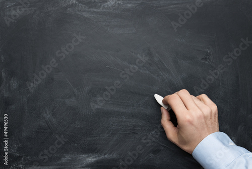 Close up of male hand writing on a blackboard with copy space