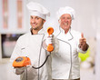 Young Chef Holding Telephone In Front Of Mature Chef