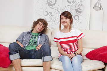 shy teenagers sitting next to each other on a sofa