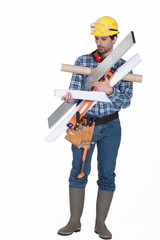 young handsome carpenter carrying miscellaneous tools
