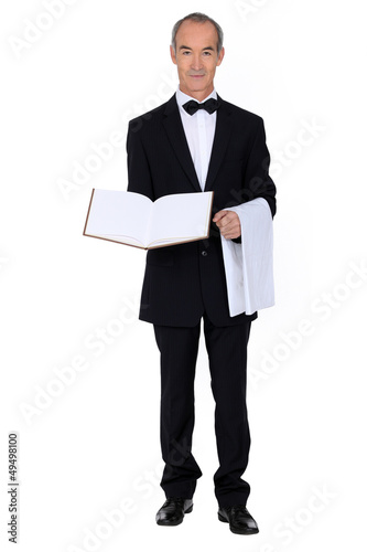 waiter is presenting a visitor book or a menu