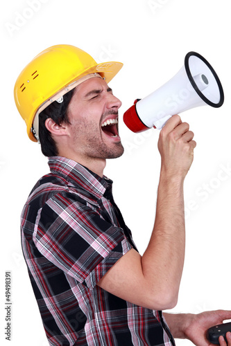 Male construction worker shouting into megaphone