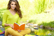 beautiful girl with book in the spring park