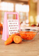 carrots with grater  on table in kitchen