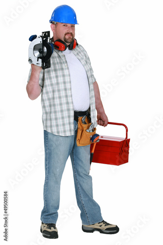 Tradesman holding a circular saw and his toolbox