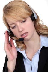 A cute blond businesswoman with a headset on.