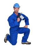 Workman holding blowtorch on white background poster
