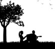 Couple in love where a guy plays guitar in park silhouette
