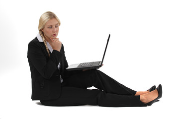 Businesswoman sitting on the floor with her laptop
