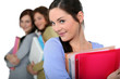 attractive female students holding folders and books