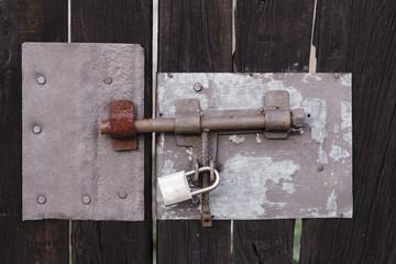 cerrojo y candado en una puerta de madera