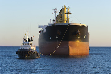 Cargo ship with tug boat assistance