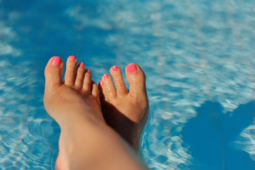 bare female feet with pink nails hanging over the water