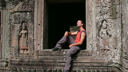 Backpacker sitting in preah khan temple, angkor, cambodia
