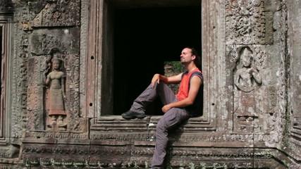 Backpacker sitting in preah khan temple, angkor, cambodia