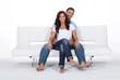 Happy couple on a sofa, studio shot