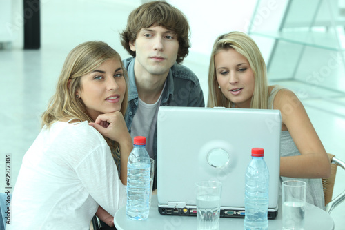 Teenagers sitting round a laptop