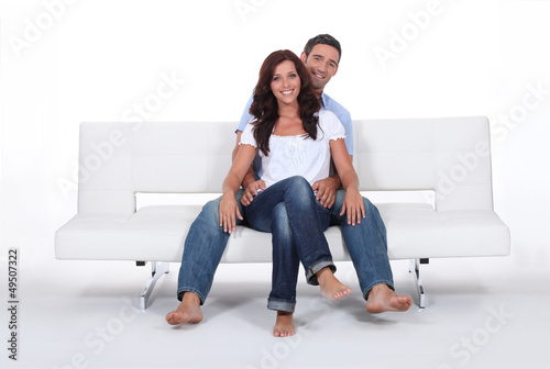 Happy couple on a sofa, studio shot
