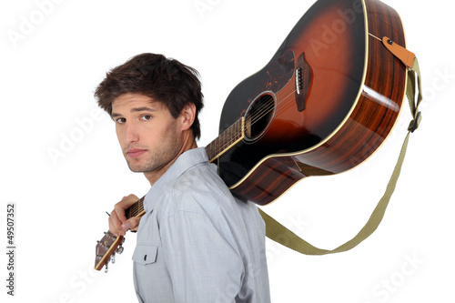 young man carrying a guitar on his shoulder