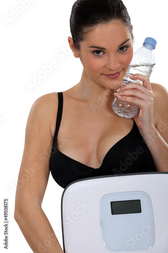 Young woman carrying scales and bottle of water