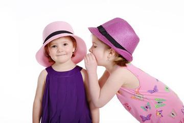 Mädchen flüstert ins Ohr, Kind schaut süß