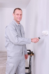 Smiling handyman painting a room white