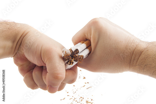 Human hands breaking cigarettes