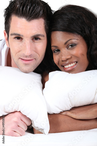 Young man and young woman smiling laid on a bed