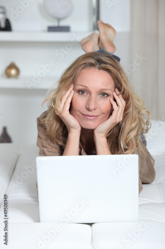 Woman lying on her stomach in front of a laptop computer