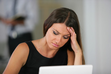 Woman with a headache at her laptop