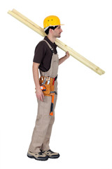 craftsman carrying two wooden boards on his shoulder
