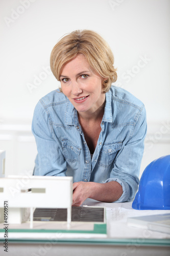 Woman with paper-work and hard hat