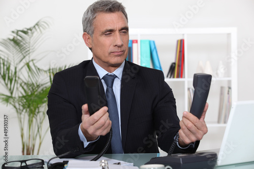 Over worked businessman holding two telephones