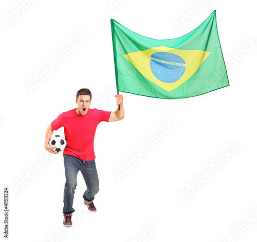 Full length portrait of an euphoric fan holding a ball and flag