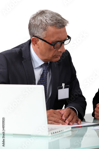 Senior businessman attentively listening to colleague
